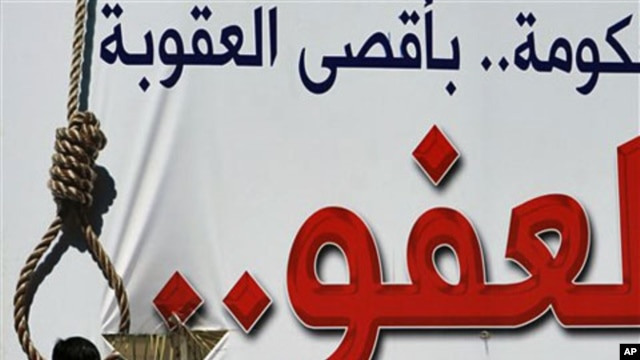 A man looks at a billboard in Muharraq demanding no leniency for those who opposed the Bahraini regime, April 28 2011