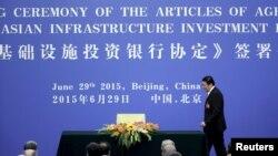 ລັດຖະມົນຕີການເງິນຈີນ ທ່ານ Lou Jiwei ຍ່າງຂຶ້ນເວທີ ໄປລົງນາມໃນຂໍ້ຕົກລົງຈັດຕັ້ງ ທະນາຄານລົງທຶນດ້ານພື້ນຖານໂຄງລ່າງຂອງເອເຊຍ ຫຼື AIIB ຢູ່ທີ່ສາລາປະຊາຊົນ ໃນປັກກິ່ງ, ວັນທີ 29 ມິຖຸນາ 2015.