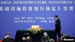 Bộ trưởng Bộ Tài chính Trung Quốc Lâu Kế Vĩ lên ký Điều khoản Đồng thuận của AIIB tại Nhân dân Đại sảnh ở Bắc Kinh ngày 29/6/2015.