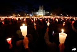 Students, friends and family hold candles up during a candle light vigil marking the second anniversary of the April 16, 2007 shootings at Virginia Tech