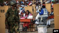 FILE: A Malawian army soldier stands guard while hundreds of residents from Ndirande township queue to vote as voting procedures are repeated after polling were disrupted yesterday, on May 21, 2014 in Blantyre.