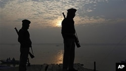 Indian police officers stand guard near the site of Tuesday's blast on the banks of the River Ganges in Varanasi, India, 08 Dec 2010