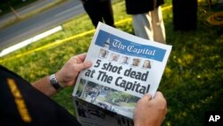 Steve Schuh, county executive of Anne Arundel County, holds a copy of The Capital Gazette near the scene of a shooting at the newspaper's office in Annapolis, Maryland. A man armed with smoke grenades and a shotgun attacked journalists in the building Thu