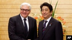 Menlu Jerman Frank-Walter Steinmeier (kiri) berpose dengan PM Jepang Shinzo Abe seusai rapat di Tokyo (11/4).