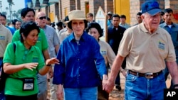 In this photo taken November 21, 2009 released by Habitat for Humanity, former U.S. President Jimmy Carter, right, holds the hand of his wife Rosalynn as they visit the Damnak Thom village where Habitat for Humanity volunteers built 21 houses, file photo.