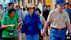 In this photo taken November 21, 2009 released by Habitat for Humanity, former U.S. President Jimmy Carter, right, holds the hand of his wife Rosalynn as they visit the Damnak Thom village where Habitat for Humanity volunteers built 21 houses.