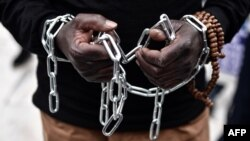 FILE - An African migrant with his hands chained takes part in a march toward the offices of the European Union during a demonstration on Dec. 2, 2017, in central Athens, protesting against the slavery of migrants in Libya.