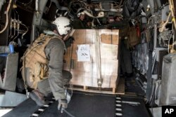 In this image provided by the U.S. Navy, Marines attached to the 26th Marine Expeditionary Unit, embarked aboard the amphibious assault ship USS Kearsarge, load military field rations at Luis Munoz Marin Airport in San Juan, Sept. 25, 2017.