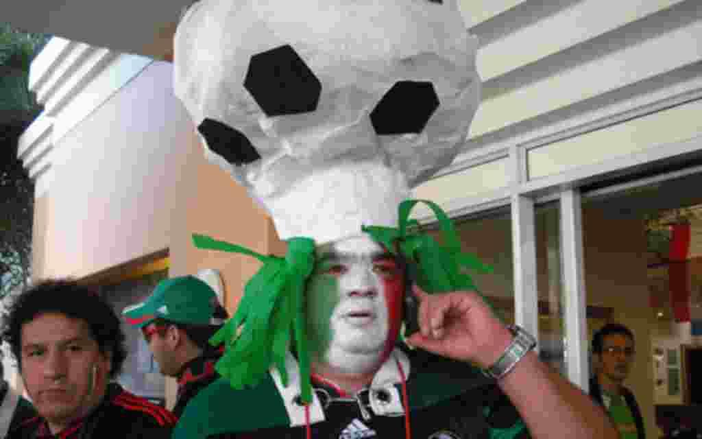 Mexicano con un balón de fútbol de sombrero, minutos antes del primer partido de su selección.