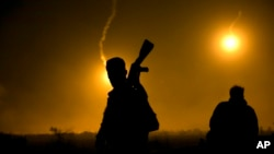 A U.S.-backed Syrian Democratic Forces (SDF) fighter watches illumination rounds light up Baghuz, Syria, as the last pocket of Islamic State militants is attacked on March 12, 2019.