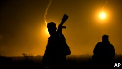 FILE - A U.S.-backed Syrian Democratic Forces (SDF) fighter watches illumination rounds light up Baghuz, Syria, as the last pocket of Islamic State militants is attacked on March 12, 2019.