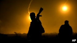 A U.S.-backed Syrian Democratic Forces (SDF) fighter watches illumination rounds light up Baghuz, Syria, as the last pocket of Islamic State militants is attacked, March 12, 2019.