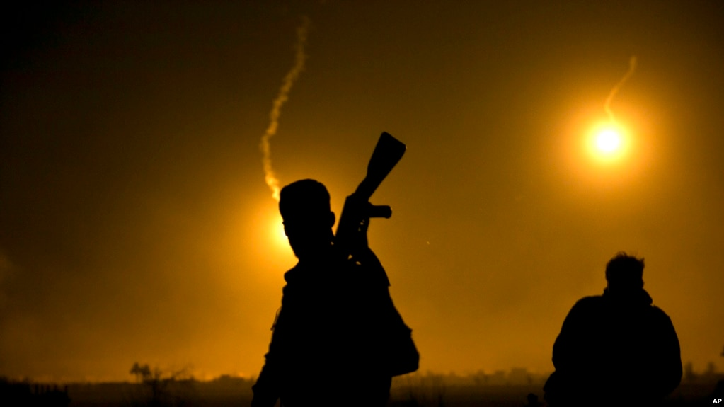FILE - A U.S.-backed Syrian Democratic Forces fighter watches illumination rounds light up Baghuz, Syria, as the last pocket of Islamic State militants is attacked on March 12, 2019.