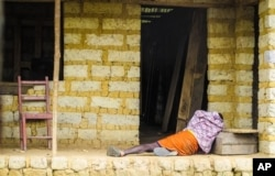 FILE - A man suffering from the Ebola virus lies on the floor outside a house in Port Loko Community, situated on the outskirts of Freetown, in Sierra Leone, Oct. 21, 2014.