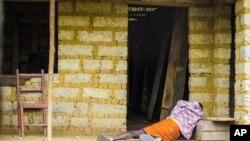 Seorang pria yang terkena virus Ebola berbaring di lantai di depan rumahnya di Port Loko Community, Freetown, Sierra Leone. (Foto: dok. AP)