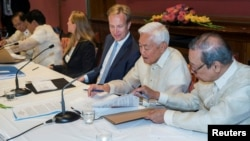 Representative of the Philippine government Jesus Dureza (R), Norwegian Foreign Minister Boerge Brende (C) and representative of National Democratic Front (NDF) Luis Jalandoni (2-R) are seen after signing an indefinite cease-fire agreement, in Oslo, Norwa
