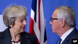 European Commission President Jean-Claude Juncker, right, greets British Prime Minister Theresa May at EU headquarters in Brussels, Wednesday, Nov. 21, 2018.