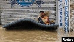 Nạn nhân lũ lụt cố giữ thăng bằng trên chiếc phà tạm bợ để di chuyển qua đường phố ngập nước ở Srinagar, ngày 7/9/2014.