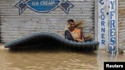 Seorang korban banjir Kashmir kehilangan keseimbangan di atas rakit buatan setelah dihantam ombak saat menuju tempat aman di Srinagar (7/9). (Reuters/Danish Ismail)