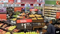 A customer selects food in the produce section of a store in Alexandria, Va., (File)