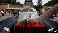 Ảnh tư liệu - Một người đàn ông đặt tay lên gần logo của một chiếc xe Rolls Royce ở Vạn Lý Trường Thành, Trung Quốc, ngày 18 tháng 9 năm 2011.