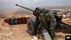 FILE -- Lebanese army soldiers work on a 130mm howitzer cannon, pointed at areas controlled by Islamic State group militants near Arsal, in northeast Lebanon, June 19, 2016.