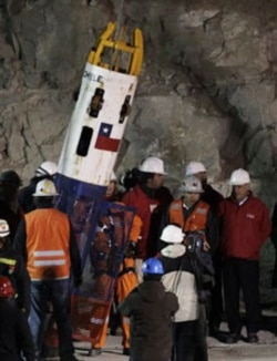 Chile's President Sebastian Pinera, far right, watches a rescue worker enter the Phoenix capsule to begin the rescue of the 33 trapped miners