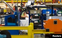 FILE - Production line workers fit parts to a Jeep Cherokee on the line at the upgraded North section of the Chrysler Toledo Assembly Complex, July 18, 2013.