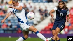 France's Camille Abily, left, attempts to stop a shot by United States' Tobin Heath during the women's group G soccer match between the United States and France prior to the start of the London 2012 Summer Olympics at Hampden Park Stadium in Glasgow, July