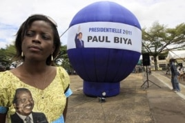 A supporter of Cameroon President Paul Biya stands next to a giant election campaign ball in Yaounde, Cameroon, October 8, 2011.