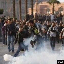 Demonstran anti Mubarak menendang gas air mata yang dilemparkan tentara Mesir untuk melerai bentrokan di Kairo, (3/2).