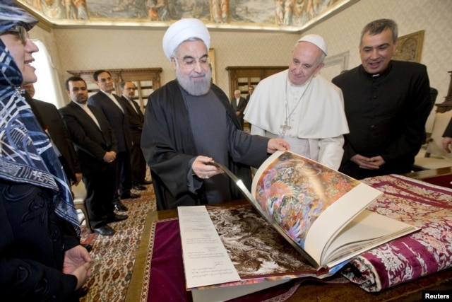 Iran President Hassan Rouhani, left, exchanges gifts with Pope Francis at the Vatican, Jan. /26, 2016.