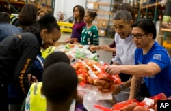 Then-President Barack Obama participates in a Thanksgiving service project by handing out food at the Capital Area Food Bank on Wednesday, Nov. 27, 2013 in Washington. The Capital Area Food Bank distributes 30 million pounds of food annually. (AP Photo)