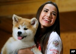 Russian Women's Olympic figure skating gold medalist Alina Zagitova holds an Akita puppy named Masaru presented by Japanese Prime Minister Shinzo Abe, in Moscow, Russia, May 26, 2018. Abe is in Russia for talks with President Vladimir Putin in hopes of making progress on joint economic projects on disputed islands as a step toward resolving a decades-old territorial row.