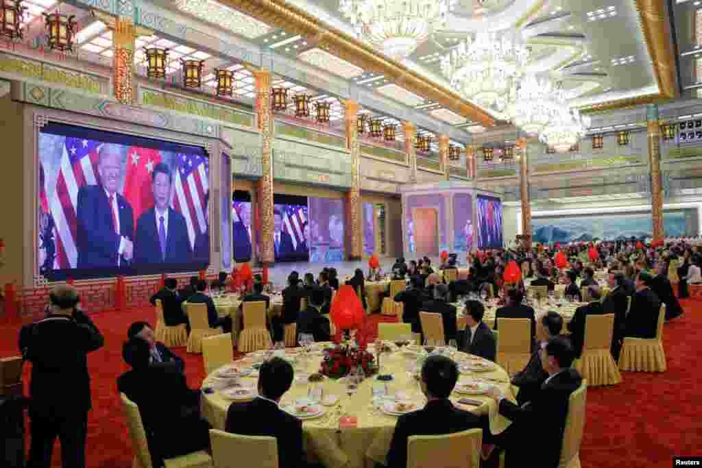 在北京人民大会堂举行的国宴上,人们观看美国总统唐纳德·川普和中国国家主席习近平会面的视频(2017年11月9日)。