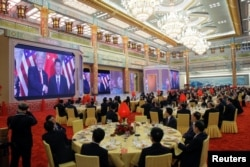 Guests watch a video about meetings between U.S. President Donald Trump and China's President Xi Jinping at a state dinner at the Great Hall of the People in Beijing, China, Nov. 9, 2017.