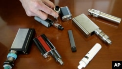 This April 10, 2018 photo shows vaping devices taken from students at Marshfield High School in Marshfield, Mass. (AP Photo/Steven Senne)