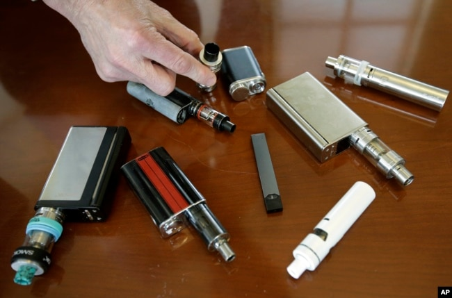In this Tuesday, April 10, 2018 photo, vaping devices that were confiscated from students in such places as restrooms or hallways at the school in Marshfield, Mass.