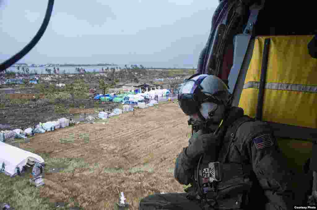 A Naval Aircrewman prepares to drop supplies, Tacloban, Philippines, Nov. 14, 2013. (U.S. Navy)