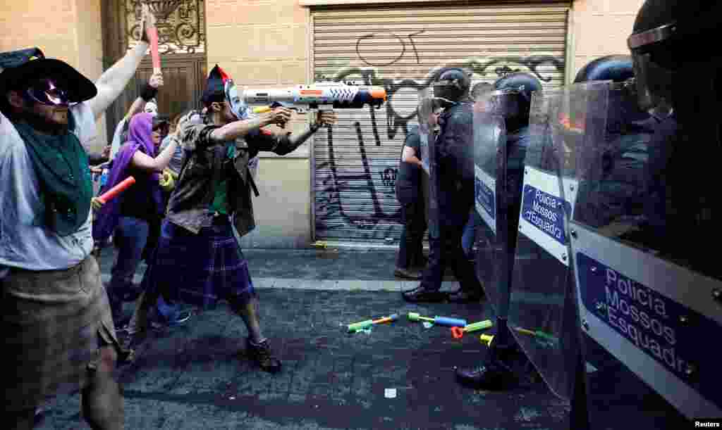 "A protester squirts a water gun at Catalan regional police in full riot gear during a protest over the eviction of squatters earlier in the week from ""The Expropriated Bank"", in Barcelona, Spain."
