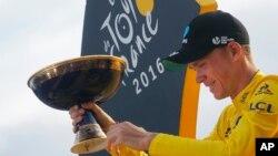 Juara Tour de France 2016 Chris Froome dari Inggris memegang pialanya di Paris (24/7). (AP/Christophe Ena)