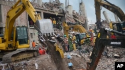 Workers and army personnel use heavy machinery as they work to clear the site and recover bodies of victims from the rubble of a garment factory building collapse in Savar near Dhaka, Bangladesh, May 6, 2013..
