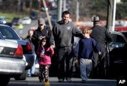 FILE - Today's high school students were young children when a shooter killed 20 children at Sandy Hook Elementary School in Newtown, Connecticut in 2012. In this photo, parents reunited with their children following the shooting at Sandy Hook Elementary School.