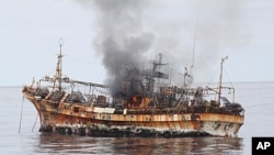 In this photo provided by the U.S. Coast Guard, a plume of smoke rises from the derelict Japanese ship Ryou-Un Maru after it was hit by canon fire by a U.S. Coast Guard cutter in the Gulf of Alaska, April 5, 2012.