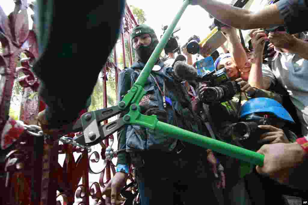 Anti-government protesters break the gate of the police headquarters during a rally in Bangkok, Jan. 22, 2014.