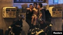 Des membres de la brigade anti-incendie française portent un homme blessé près de la salle de concert Bataclan après la fusillade mortelle à Paris, France, 13 novembre 2015.
