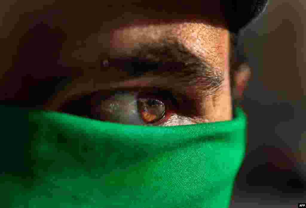 March 29: In Tripoli, a pro Gadhafi supporter wears a green scarf on his face. (AP Photo/Jerome Delay)