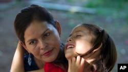 """Araceli Ramos tiene a su hija Alexa de 5 años en su regazo durante una entrevista en un parque en San Miguel, El Salvador, el 18 de agosto de 2018. El gobierno federal ofrece a todos los padres deportados la oportunidad de llevar a sus hijos con ellos, pero Ramos dijo que le ordenaron firmar una renuncia para dejar a Alexa atrás. """"El agente puso su mano sobre la mía, él tomó mi mano, me obligó a firmar"""", dijo. (Foto AP / Rebecca Blackwell)"""