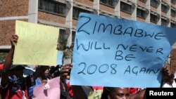 FILE: Zimbabweans hold placards during a protest against President Robert Mugabe government's handling of the economy in Harare, Zimbabwe, August 3, 2016.