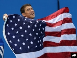United States' Michael Phelps walks with his national flag during the medal ceremony for the men's 4 x 100-meter medley relay final during the swimming competitions at the 2016 Summer Olympics, Sunday, Aug. 14, 2016, in Rio de Janeiro, Brazil.